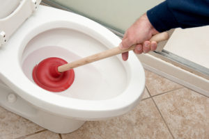 A plumber uses a plunger to unclog a toilet